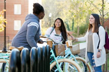 Three students talk around a bicycles rack.