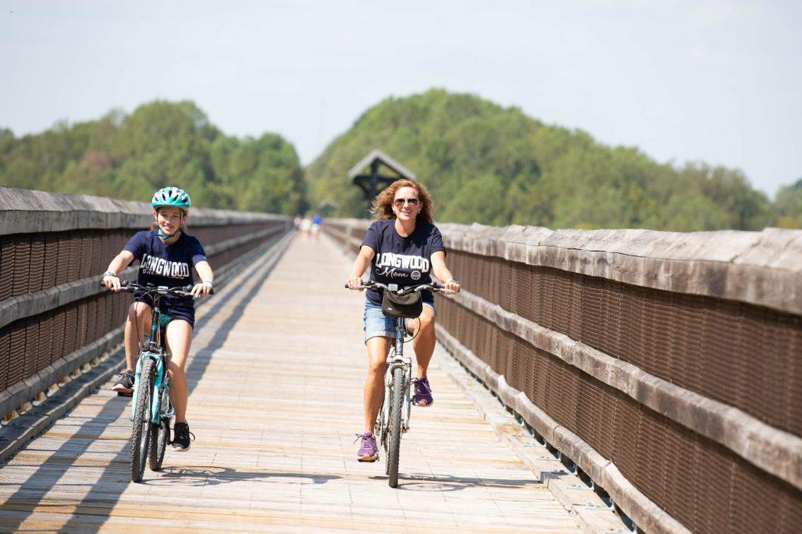 Two people biking across High Bridge