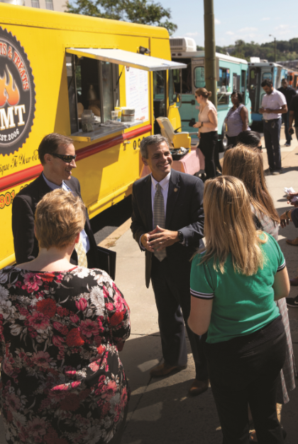 Food trucks come to Capitol Square during lunchtime each week as part of Gov. Ralph Northam's OnTheSquareVA initiative, which promotes activities for state employees in the area. Damico (center) oversees the program.