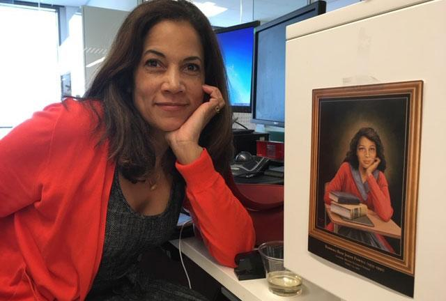 Sydney Trent is pictured with a photo of her godmother, Barbara Johns, at her desk in the Washington Post newsroom.