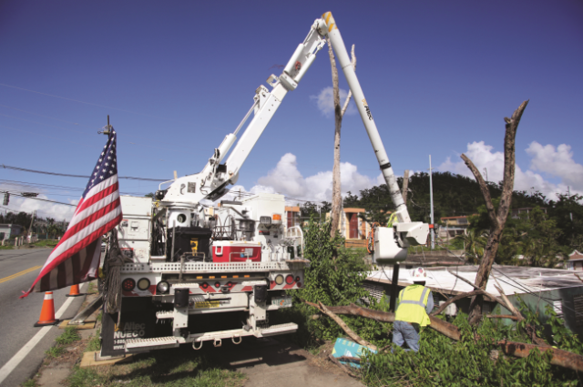 An electric utility crew from the mainland works on a line more than three months after Hurricane Maria cut it.