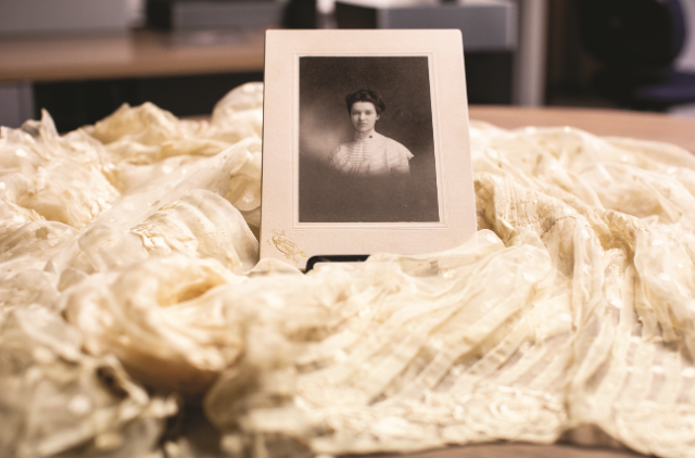 A photo of Mary Venable Cox Mattoon, Class of 1900, is surrounded by her wedding dress. Both items are in the Greenwood Library archives. The photography of Mattoon's great-great-granddaughter, Eva O'Leary, is currently on exhibit at the Longwood Center for the Visual Arts.