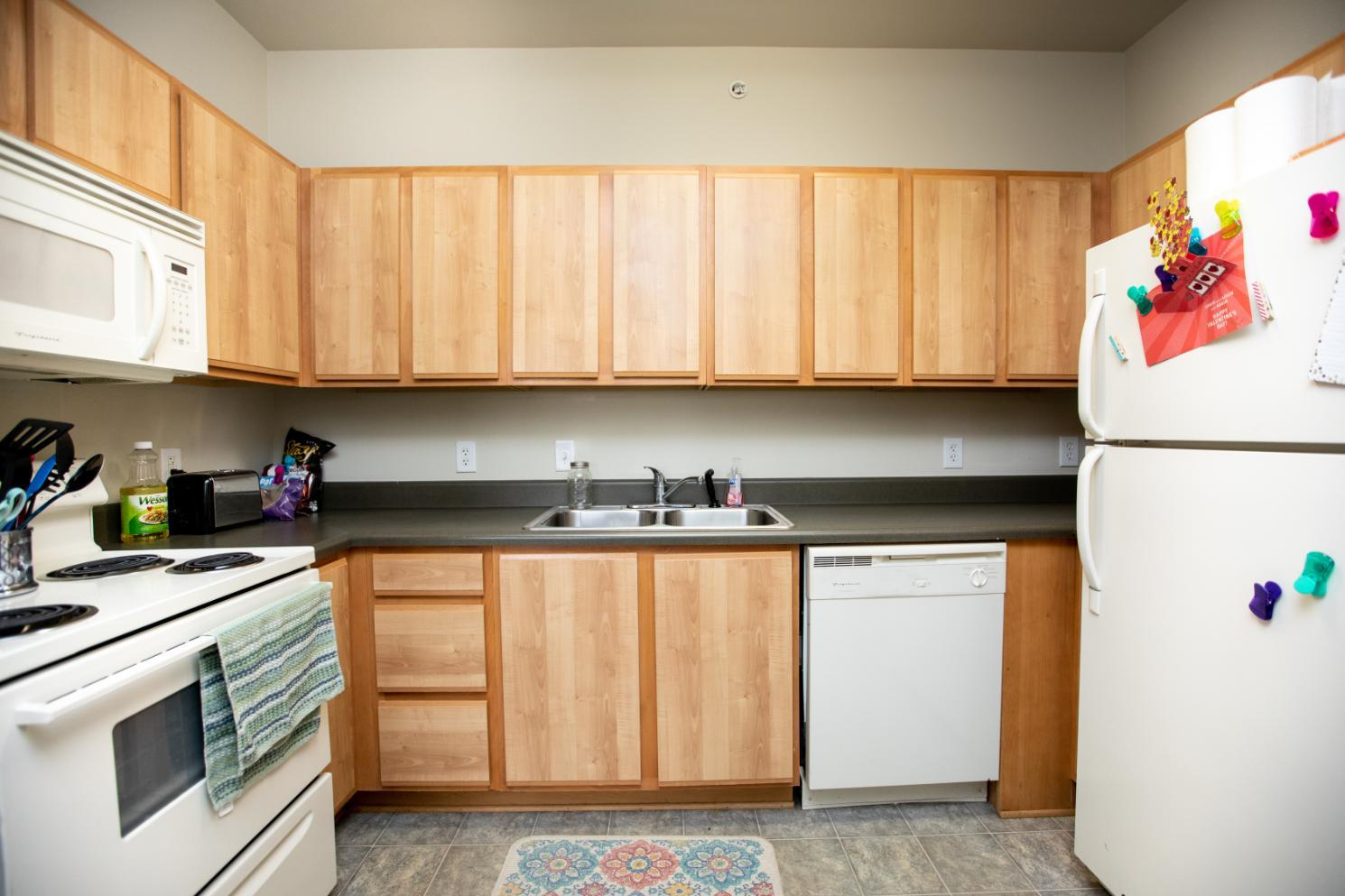 Longwood Landings 4 Bedroom Apartment ; Kitchen with stove, dishwasher, oven, microwave over stove, double sink, refrigerator, wall cabinets and counter cabinets.