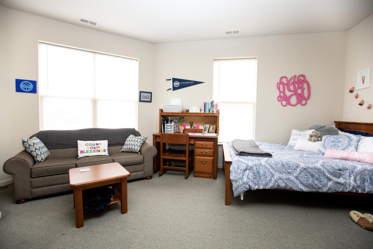 Longwood Landings Studio Apartment; View of bed and couch and windows from the kitchen