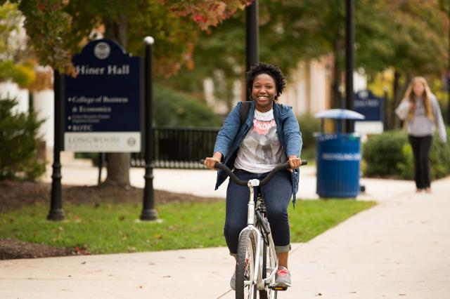 Student riding down Brock Commons on a bike