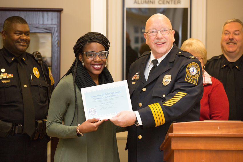 Deja Mills '17 is named winner of Selfies with the Longwood Police by Chief Bob Beach. Behind are Lt. John Johnson (left) and Lt. Ray Ostrander (right)