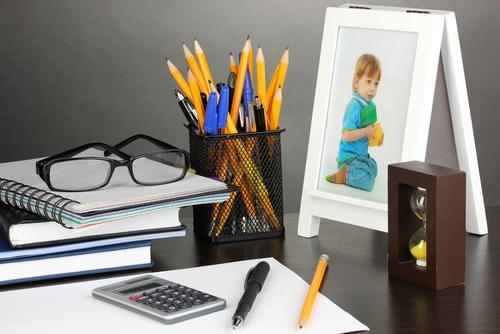 A desk, including a photo of a child. Image courtesy of Shutterstock