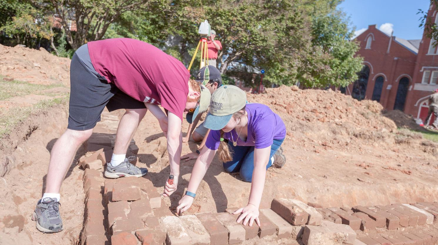 In a class-related archaeology survey, Ashton Chandler '18, an anthropology major from Leesburg, and Jessica Keaton '17, an anthropology major from Forest, uncover the foundation of the Richardson House in Bicentennial Park, which stood where the new admissions building will be built.