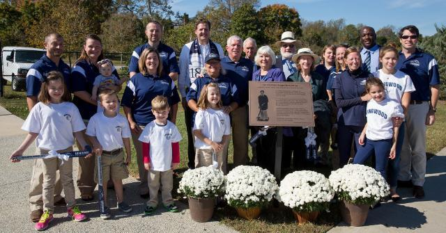 Dr. Jackson's family and friends stand near the special plaque that will reside on the concourse of Burger Jackson Field at the Longwood Athletics Complex.