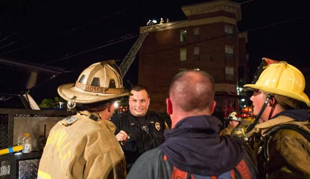 LUPD Sgt. Walter Whitt, who was the first to smell smoke in the Landings building and helped evacuate the building, talks with fire crews the night of the fire.