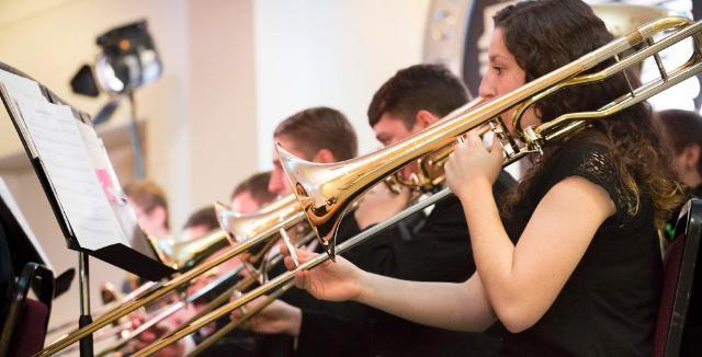 Longwood student playing the trombone in holiday concert performance