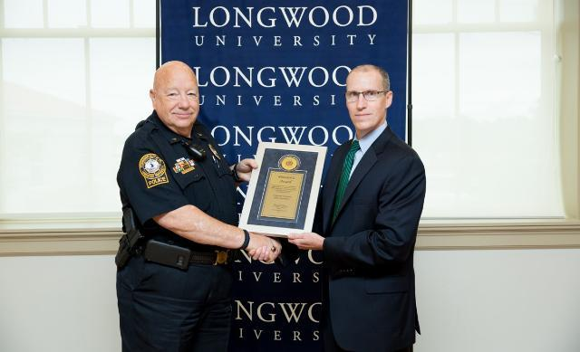 Longwood Police Chief Bob Beach accepts the award from Jerald W. Page, special agent in charge of the Secret Service's Richmond Field Office