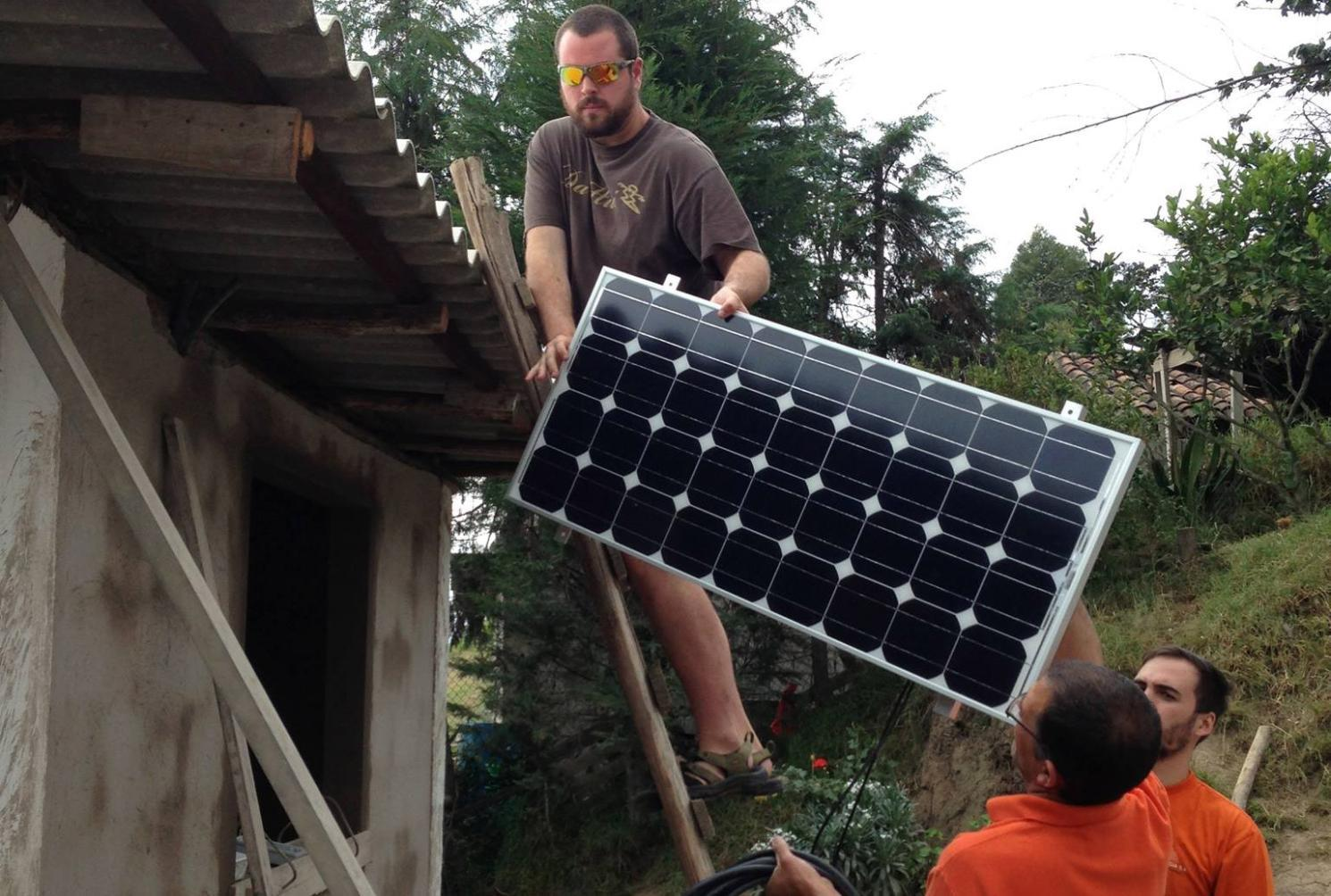Then-Longwood student Matt Doxey installs a solar panel on a medical clinic during a trip to Ecuador with Dr. Chuck Ross.