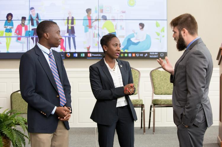 Longwood junior Joseph Hyman speaks with Traci DeShazor, deputy secretary of the commonwealth, and Praise Nyambiya after a roundtable discussion on boosting millennial civic engagement hosted by Longwood last fall.
