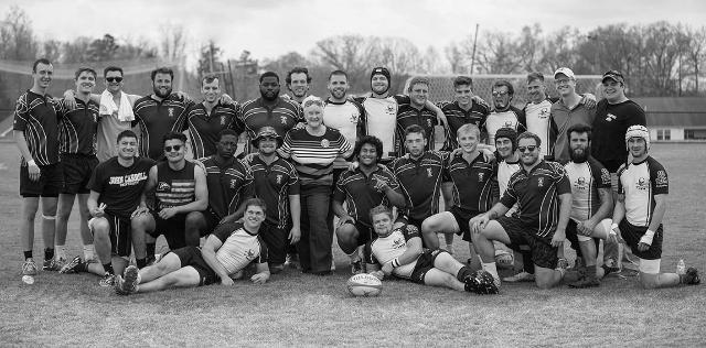 Ellie Miller stands with the 2018 Longwood men's rugby team at the annual Todd Miller Memorial Rugby Tournament. Miller presented two players—a male and female rugger—with the newly endowed Todd Miller scholarship.