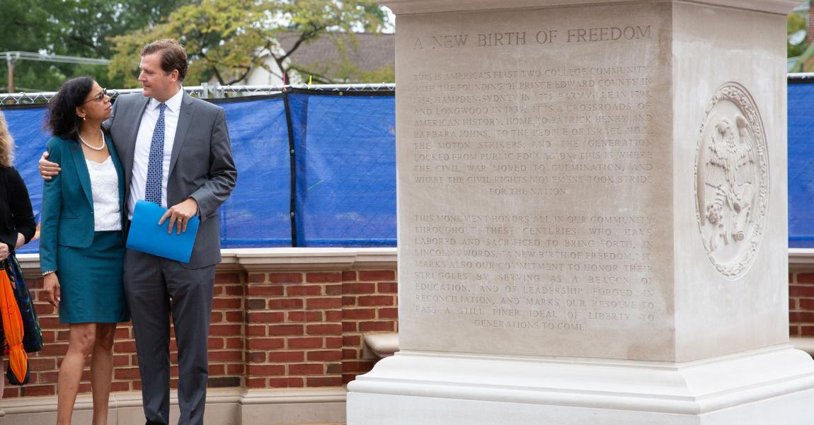 Longwood President W. Taylor Reveley and Board of Visitors member Nadine Marsh-Carter embrace at the dedication of a new monument in Farmville dedicated to the history of the area and those who fought to expand American liberty.