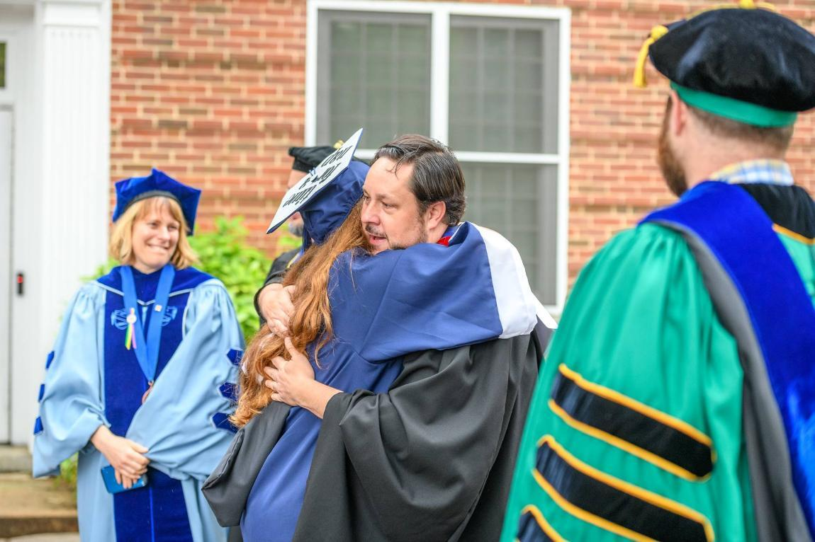 Dr. Halliday hugging a student during Commencement 2018