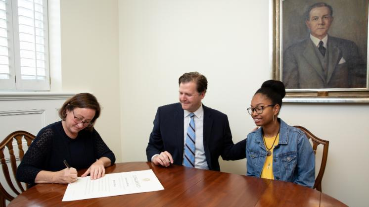 Chaniece Williams '19 and President W. Taylor Reveley IV watch as Marianne Radcliff '92, rector of the Board of Visitors, signs Williams' Longwood diploma last month.