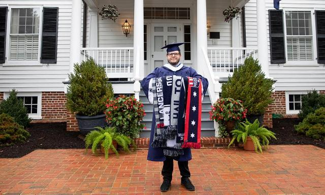 Bradley Phelps '20 stands in front of the Longwood House, proudly holding his collection of Longwood scarves, a unique tradition associated with The G.A.M.E. event each year.