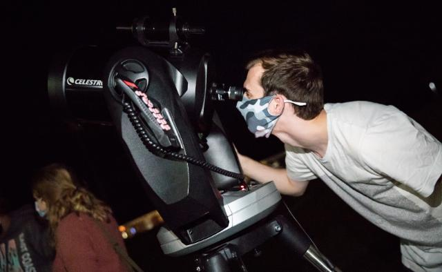 Austin Hedges '21, president of the Society of Physics Students, sets up the telescope for the evening's stargazing. The telescope has a GPS system that is programmed with the locations of thousands of celestial objects.
