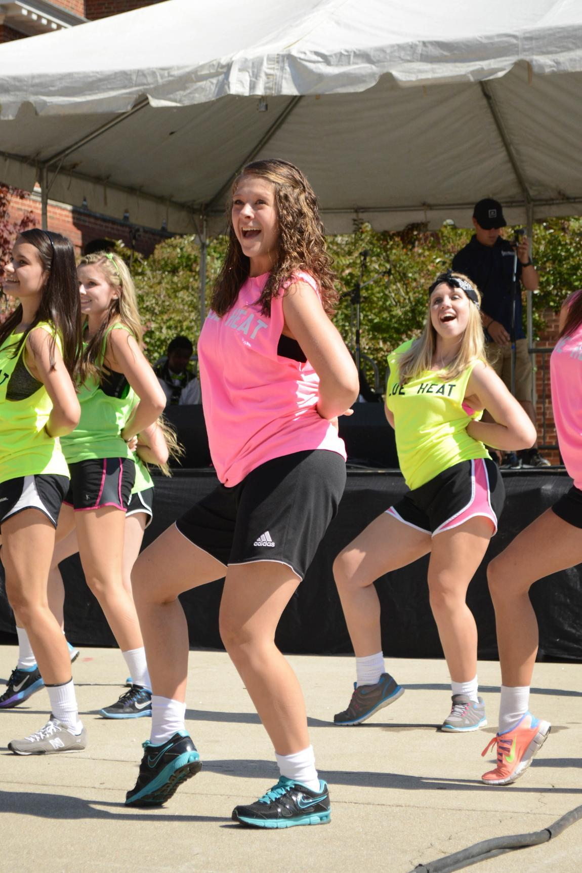 Young women perform a dance in brightly colored tank tops at Oktoberfest