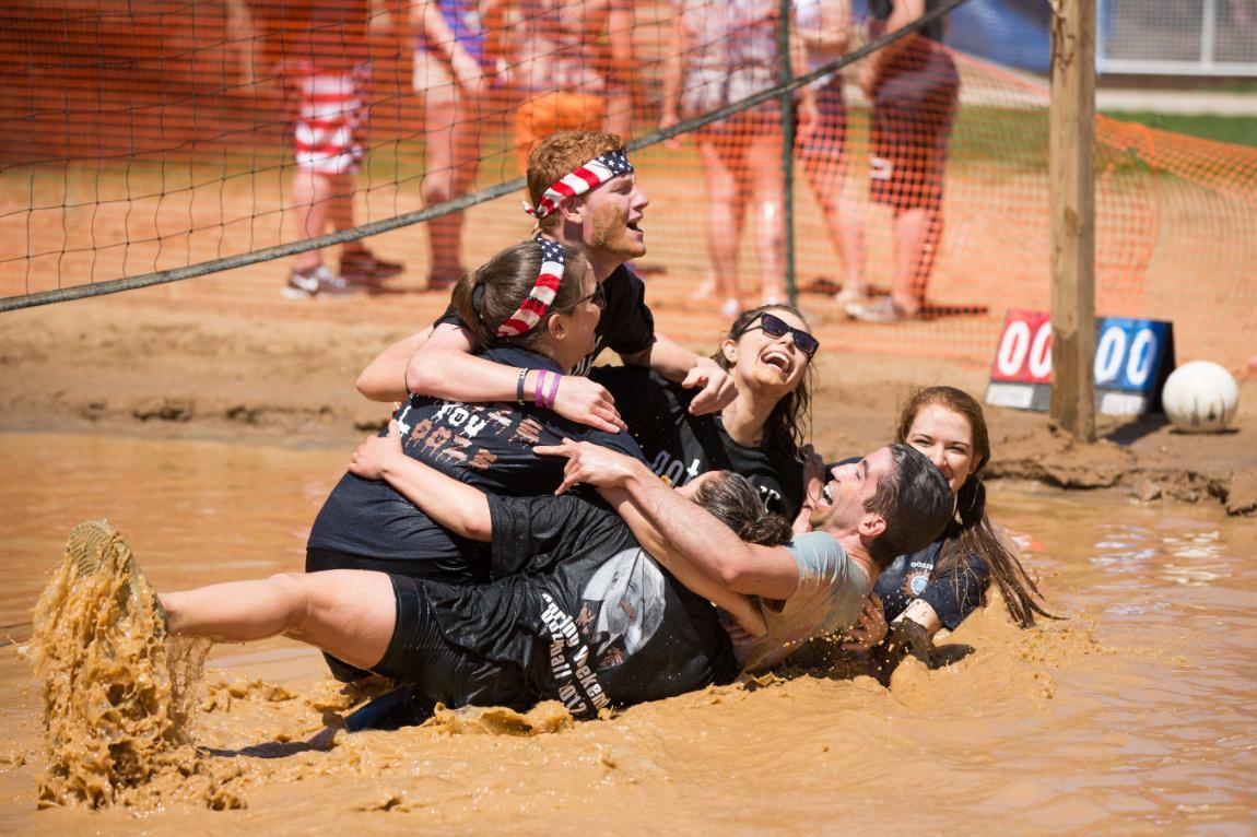 Longwood students collapse in a pile, laughing, during a game of volleyball in the mud