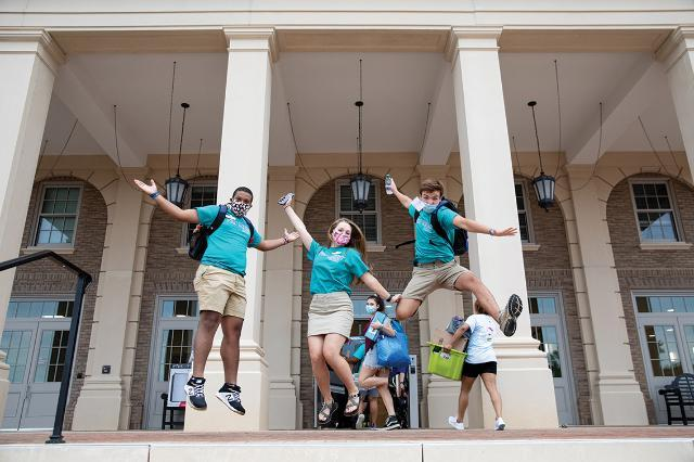 Student Ambassadors jumping outside one of the high rise residence halls