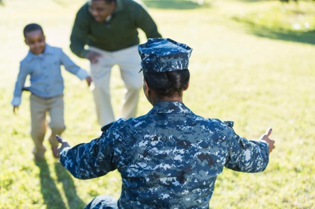 A military homecoming. rear view of an African American woman wearing a navy camouflage uniform, arms outstretched ready to welcome her little boy who is running toward her with his father.